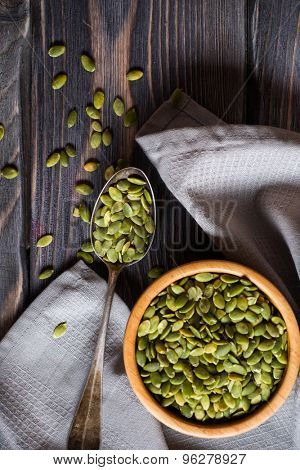 Raw Organic Pumpkin Seeds in a Bowl over wooden background