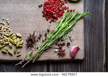 Spices over wooden background with empty place for text. Rosemary, cardamom, pepper corns, garlic and sea salt.