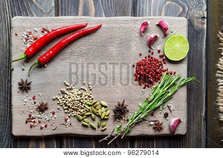 Spices over wooden background with empty place for text. Chili pepper, cardamom, pepper corns, rosemary and sea salt.