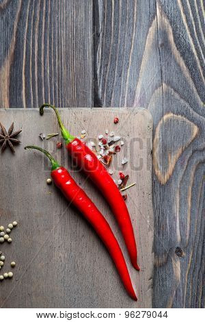 Red hot chili pepper and mixed pepper corns over wooden background