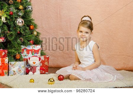 Five-year Girl Sitting At The Christmas Tree