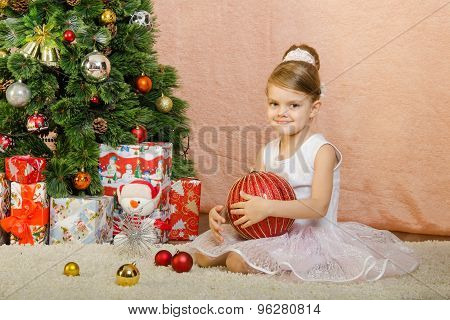 Five-year Girl Sitting At The Christmas Tree With A Large Ball