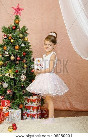 Five-year Girl Standing With Toy Snowman At Christmas Tree