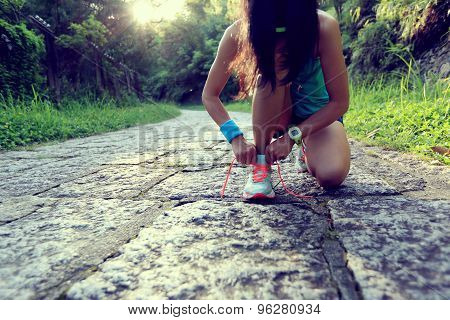 young woman runner tying shoelaces on stone trail