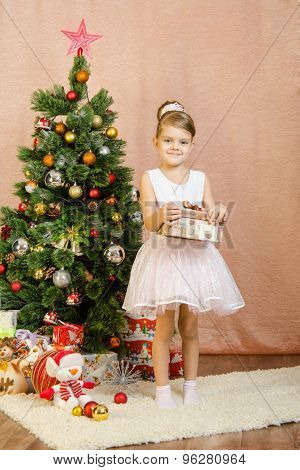 Five-year Girl With A Gift Stands Near Christmas Tree