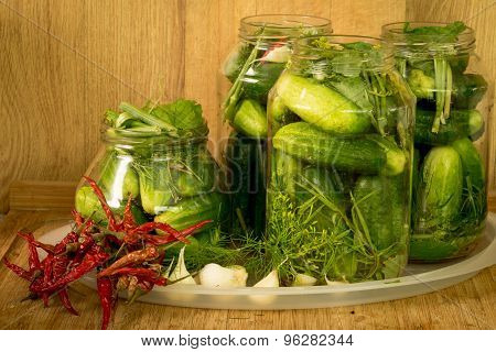 Homemade Salted Cucumbers In A Glass Jar On The Background Of Fresh Cucumbers, Garlic, Dill And Pepp