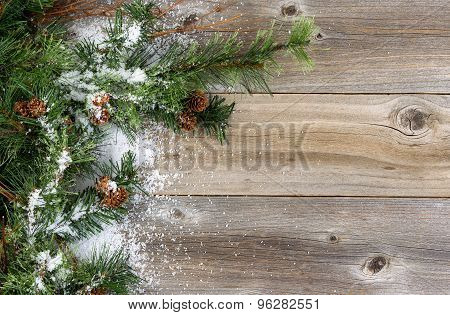 Rough Fir Branches Covered In Snow On Rustic Wooden Boards