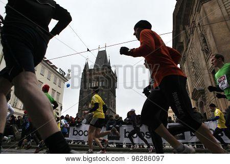 PRAGUE, CZECH REPUBLIC - APRIL 6, 2013: Athletes run past the Old Town Bridge Tower of the Charles Bridge during the Prague international marathon in Prague, Czech Republic.