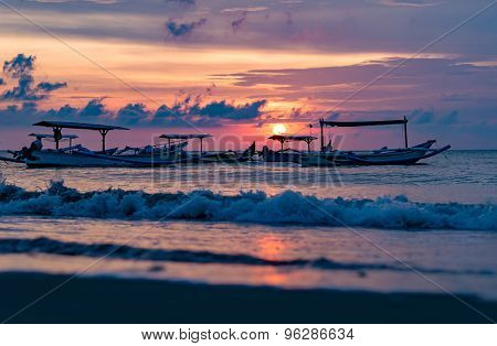 traditional Balinese ships Jukung close on Sanur beach at sunrise, Bali, Indonesia