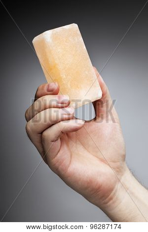 Man holding a himalayan salt soap bar, used for cleansing the skin or as a deodorant.