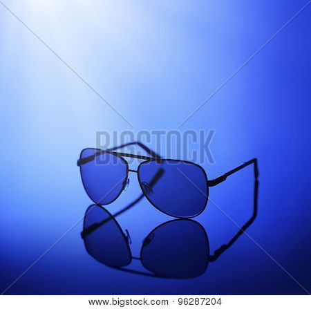 Sunglasses in blue light on a reflective background.