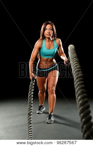 Portrait of young woman working out with heavy ropes over dark background