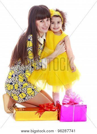 Beautiful fashionable long-haired mom in short dress hugs your f