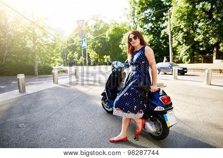Young woman sitting on the scooter