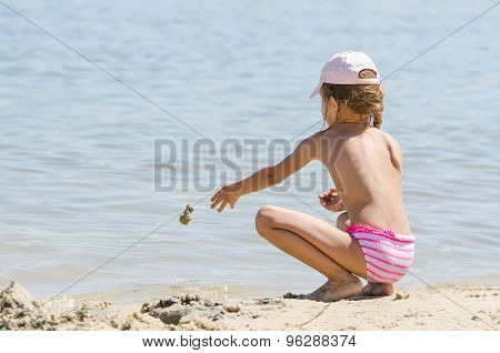 Girl On The River Throws Sand In Water