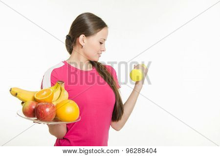 Girl Athlete Dumbbell Raises His Hand And Other Holding A Fruit