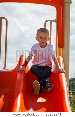 Child In Playground Boy Playing On Slide