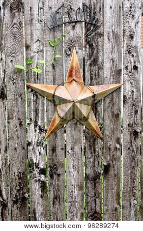 Rusty Star & Welcome sign on Weathered Wood Fence