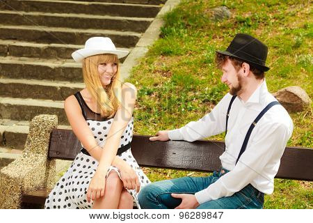 Couple Retro Style Sitting On Bench In Park