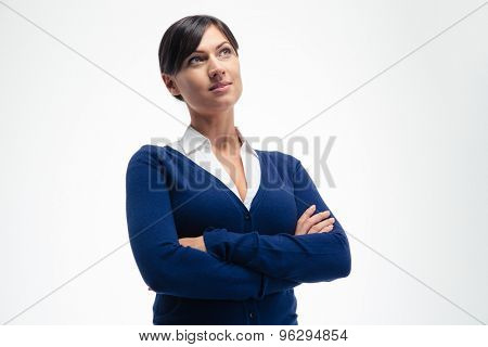 Happy thoughtful businesswoman standing with arms folded isolated on a white background. Looking up