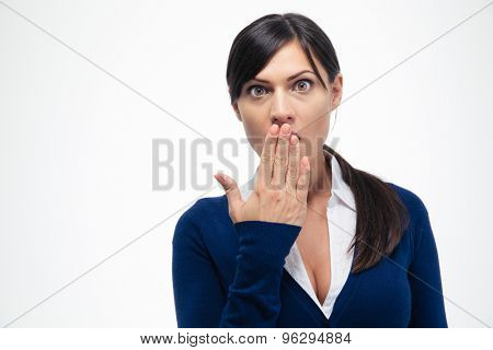 Portrait of amazed businesswoman covering her mouth and looking at camera isolated on a white background