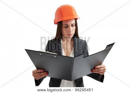 serious businesswoman in orange hardhat holding black folder and reading documents. isolated on white background