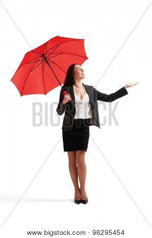 businesswoman with red umbrella held out her hand and looking up. isolated on white background