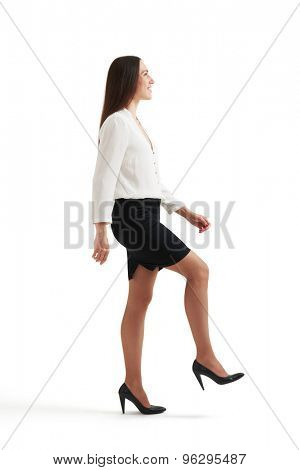 smiley businesswoman in formal wear doing one step and looking up. isolated on white background