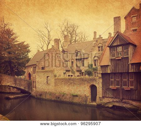 Bruges' canal  near Church of Our Lady, Belgium. Photo in retro style. Added  paper texture.