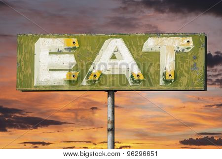 Faded vintage eat sign with sunset sky.