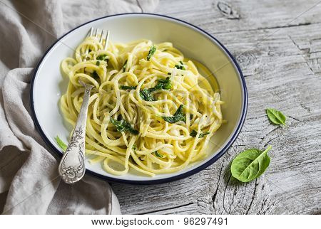 Pasta With Spinach And Cream Sauce On Vintage Enameled Plate On A Light Wooden Background