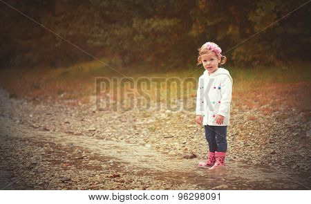 Sadness Cute Baby Girl  In The Rain Playing On Nature