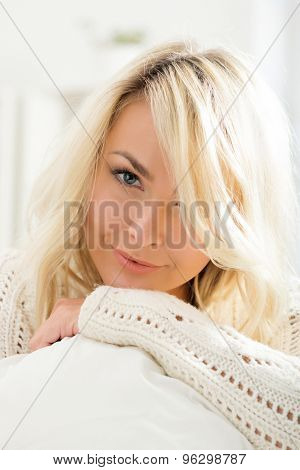 Beautiful smiling woman laying on a pillow in the morning.