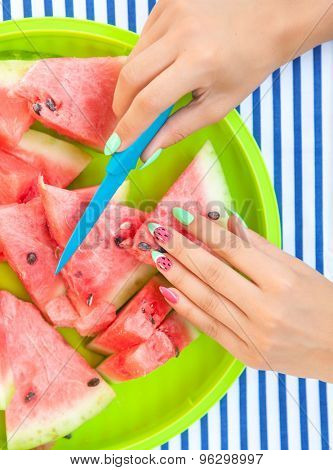 Hands close up of young woman with watermelon manicure cutting watermelon fruit, summer manicure nail art and food concept
