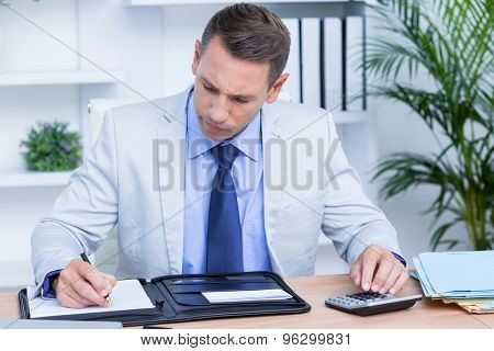 Professional businessman writing on his notebook in the office