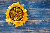 stock photo of poblano  - Guacamole with avocado tomatoes mexican food on blue wood - JPG
