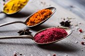 pic of saffron  - Different spices selection in old metal spoons over wooden background - JPG