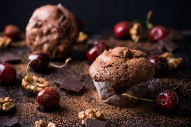 stock photo of chocolate muffin  - Chocolate muffins on dark background cocoa powder walnuts cherries and chocolate chunks as decoration selective focus - JPG