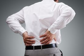 picture of medical condition  - Backache concept bending over in pain with hands holding lower back - JPG