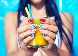 picture of marines  - Young woman with marine sailor manicure holding glass of orange juice - JPG