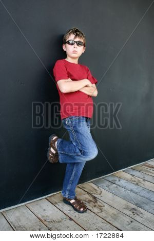 Child Leaning Against Dark Wall