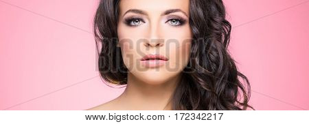 Portrait of beautiful brunette over pink  background. Beauty concept.