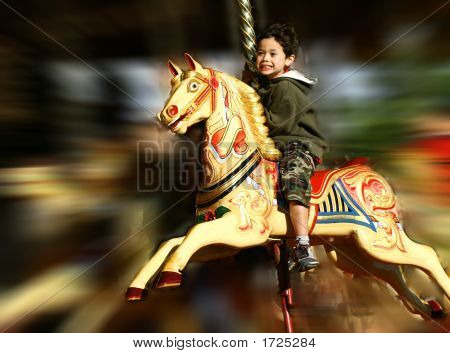 Excited Little Boy On Fast Moving Carousel