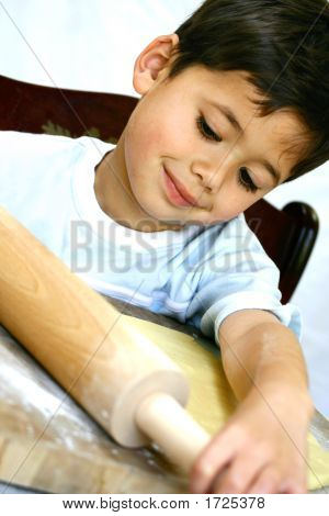 Boy Using Rolling Pin On Cookie Dough