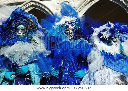 Three Masks Dressed In Blue Costumes At St. Mark's Square During Venice carnival