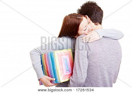 Frau mit Geschenk umarmen Mann