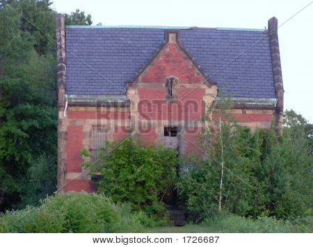 Old Brick Building Surrounded by Shrubs