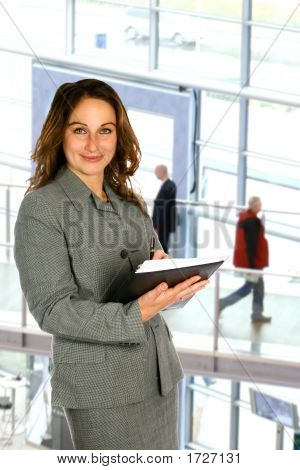 Sales Representative Holding Notebook In Corporate Interior