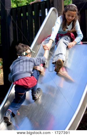 Boy And Girl Climbing Up Slide At Playground