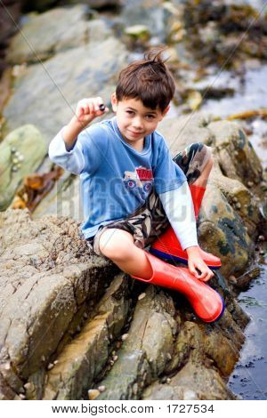 Young Boy With Snail Found In A Rock Pool